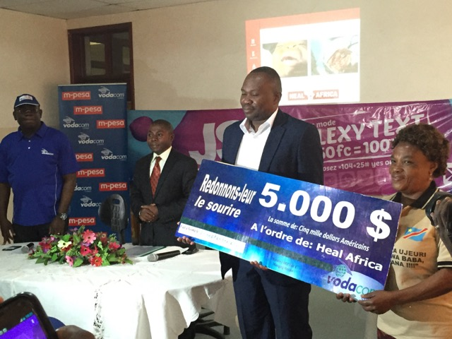 HEAL Africa Hospital Chief operating officer receives cheque from Vodacom and Minsiter of Health